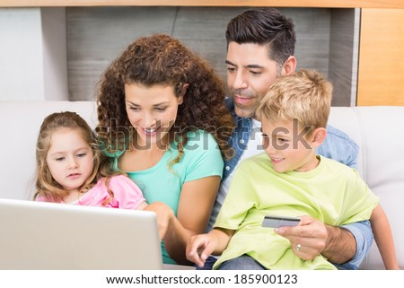 Cheerful family sitting on sofa with laptop shopping online at home in living room - stock photo