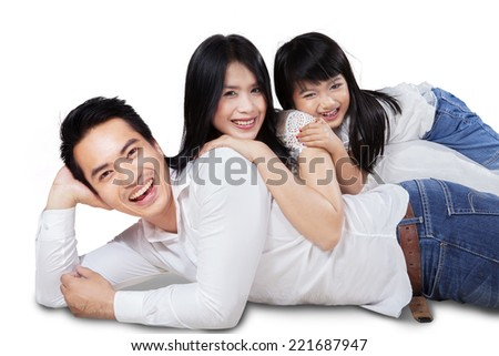 Cheerful family smiling at camera while lying and cuddling in studio - stock photo