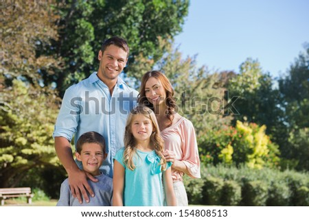 Cheerful family standing in the countryside smiling at camera - stock photo