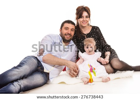 Cheerful family with baby girl sitting on fluffy blanket - stock photo