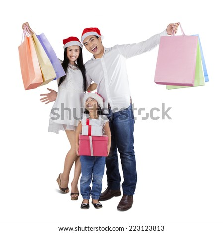 Cheerful family with shopping bags and christmas gift celebrate christmas day - stock photo