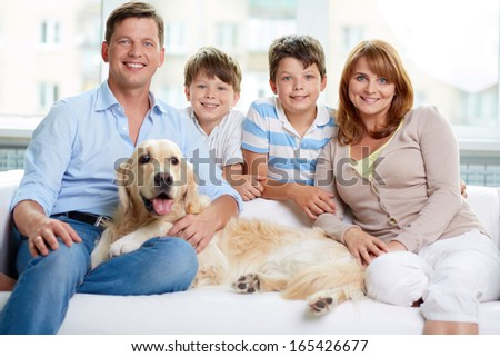 Cheerful family with their pet sitting on sofa at home - stock photo