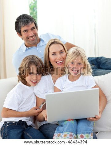 Cheerful family working at a computer sitting on sofa - stock photo