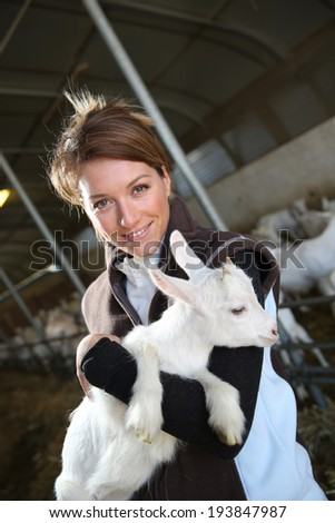 Cheerful farmer woman carrying baby goat in barn - stock photo