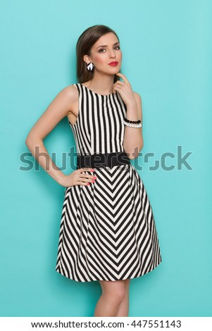 Cheerful fashion model in striped dress posing with hand on hip. Three quarter length studio shot on turquoise background. - stock photo