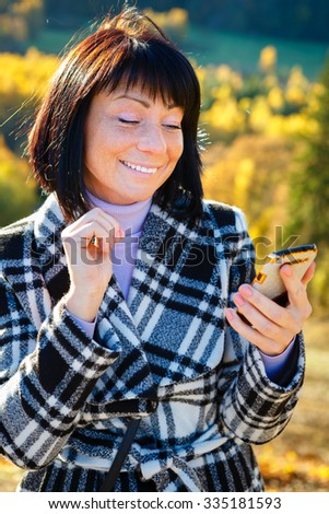 Cheerful fashion woman 40 years old wearing warm clothes in autumn. Beautiful brunette with autumn coat. Smiled and reading sms on her smartphone, Gold autumn background - stock photo