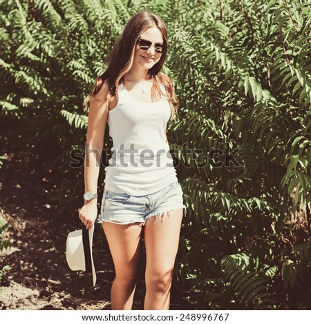 Cheerful fashionable woman in stylish hat and jeans shorts posing. Hipster style. Photo with instagram style filters - stock photo