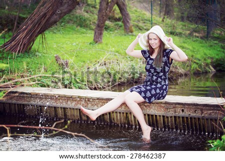Cheerful fashionable woman sits on small bridge and splashing water by her legs in warm spring day. - stock photo