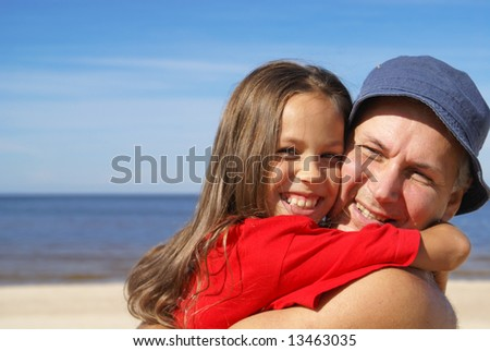 Cheerful father and daughter on a beach - stock photo