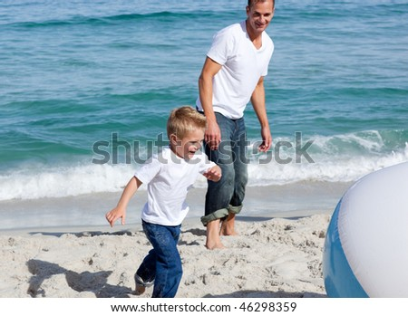 Cheerful father and his son playing with a ball at the beach - stock photo
