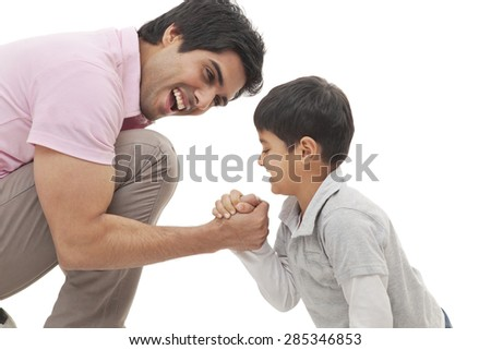 Cheerful father and son arm wrestling over white background - stock photo