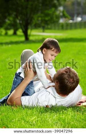 Cheerful father and son lie on a lawn in a summer garden - stock photo