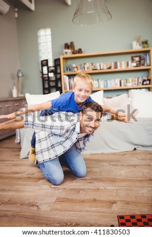Cheerful father and son playing on hardwood floor at home - stock photo