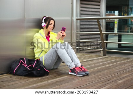 Cheerful female athlete texting message or email on smartphone on a urban fitness workout break. Sporty woman looking her cellphone. - stock photo