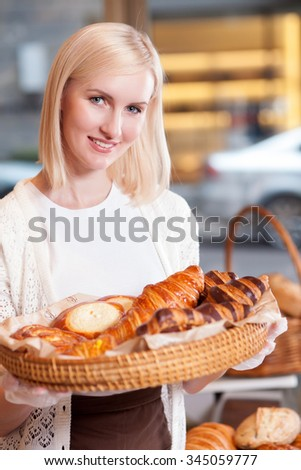 Cheerful female baker is selling pastry. She is standing and holding a basket of fresh buns. The woman is looking at camera and smiling - stock photo