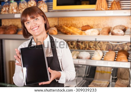 Cheerful female baker is showing a tablet with recipe to the camera. She is standing near shelf of baked products and smiling. Copy space in right side - stock photo