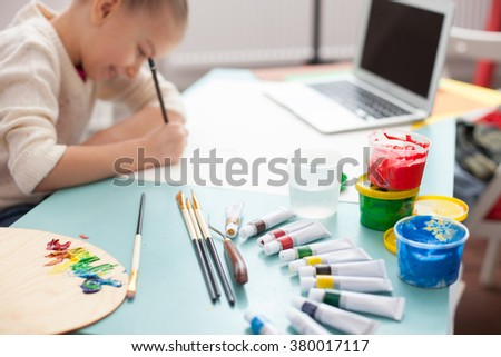 Cheerful female child is painting at home - stock photo