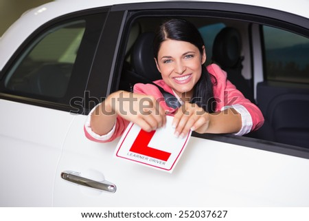 Cheerful female driver tearing up her L sign at new car showroom - stock photo