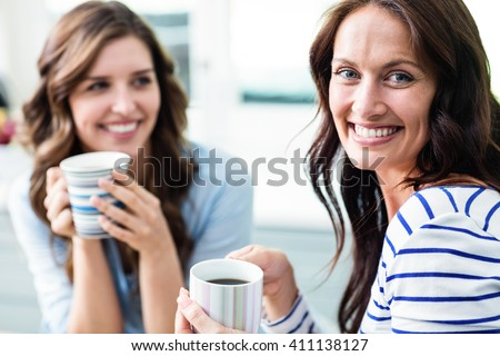 Cheerful female friends holding coffee mugs while sitting at table in kitchen - stock photo