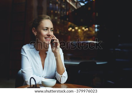 Cheerful female talking on mobile phone with friend while sitting with cup of cappuccino in modern coffee shop, smiling businesswoman having nice cell telephone conversation during work break in cafe - stock photo