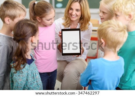 Cheerful Female Teacher Showing a Tablet Computer with Blank Screen While Teaching the Kids Inside the Classroom. - stock photo