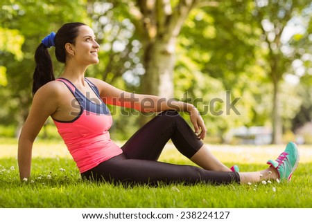 Cheerful fit brunette day dreaming on the grass in the park - stock photo