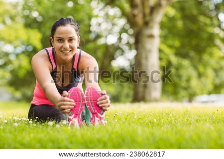 Cheerful fit brunette stretching on the grass in the park - stock photo
