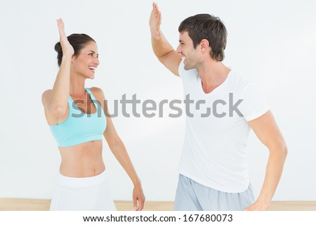 Cheerful fit young couple giving high five in the fitness studio - stock photo