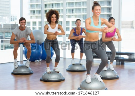 Cheerful fitness class and instructor doing pilates exercise in bright room - stock photo