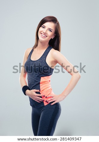 Cheerful fitness woman posing over gray background and looking at camera - stock photo