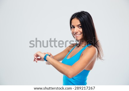 Cheerful fitness woman using fitness tracker over gray background. Looking at camera - stock photo