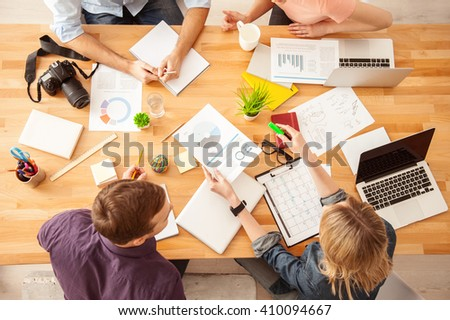 Cheerful four young colleagues are working together - stock photo