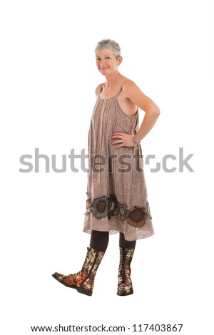 Cheerful friendly older woman stands in flowered boots and brown cotton shift dress. She has short gray hair. Isolated on white background, vertical. - stock photo