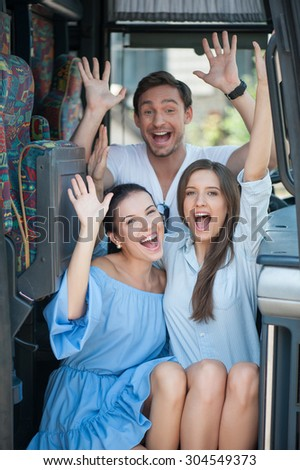 Cheerful friends are sitting on doorsteps of a bus. They are raising their hands up and smiling. The women are embracing. The man is sitting behind them - stock photo