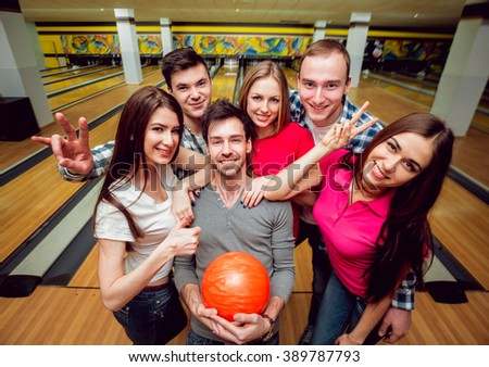 Cheerful friends at the bowling alley with the balls. Selfie - stock photo
