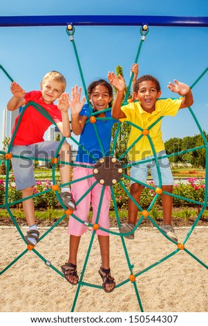 Cheerful friends climbing the net at a city playground - stock photo