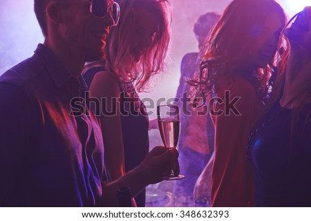 Cheerful friends enjoying party in nightclub - stock photo