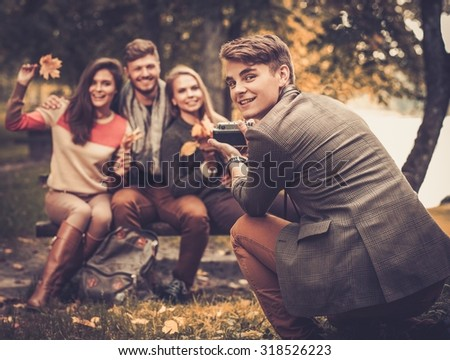 Cheerful friends in autumn park taking picture - stock photo