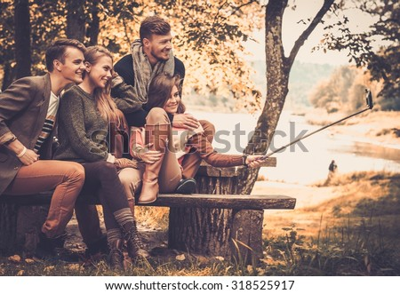 Cheerful friends in autumn park taking selfie - stock photo