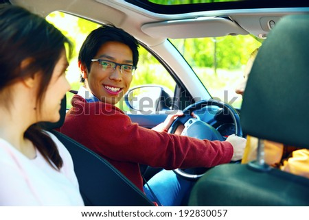 Cheerful friends in the car ready for vacation - stock photo