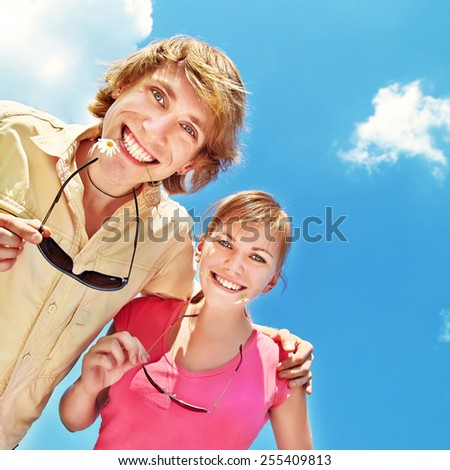 cheerful friends in the summer on a background sky.  young people having fun outdoors - stock photo