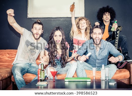Cheerful friends sitting on the couch and exulting while watching a sport match on tv - Happy young cool people having fun at a home party - stock photo