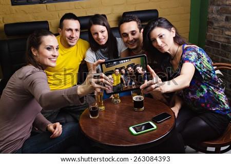 Cheerful friends taking selfie in pub using digital tablet - stock photo