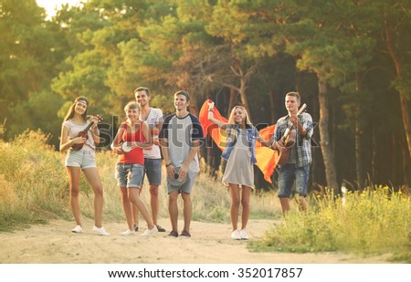Cheerful friends walking on footpath near the forest - stock photo