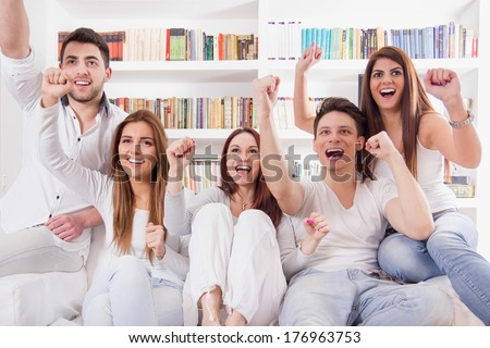 cheerful friends watching game on tv cheering - stock photo
