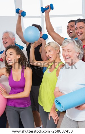 Cheerful friends with hands raised holding equipment in fitness studio - stock photo