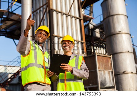 cheerful fuel chemical workers working at refinery plant - stock photo