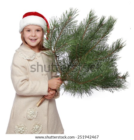 Cheerful funny little girl with blond hair in a red Santa hat holding a bush natural pine - stock photo
