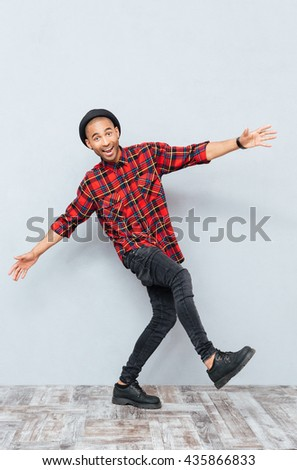 Cheerful funny young man dancing and having fun - stock photo