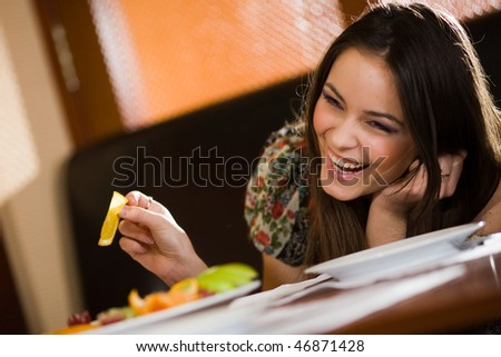 Cheerful girl at table - stock photo